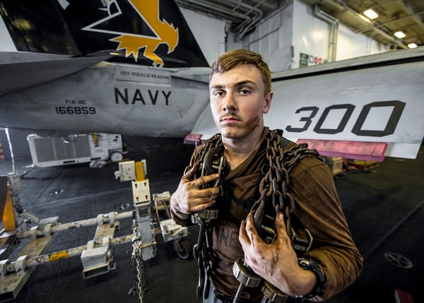 Airman Alex Rogers stands in the hangar bay of the Japan-based carrier Ronald Reagan. Sailors like Rogers used hard work and a rededication to the basics to cope with 7th Fleet tragedies, one officer said. (MC3 Ryan McFarlane/Navy)