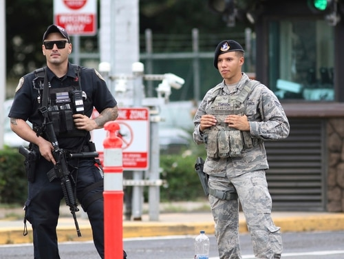 Security stands outside the main gate at Joint Base Pearl Harbor-Hickam on Wednesday in Honolulu. (Caleb Jones/AP)