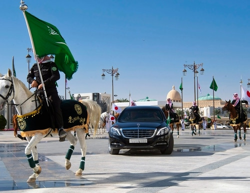 The convoy of Japan's Prime Minister Shinzo Abe is surrounded by an honor guard as he arrives at the Royal palace to meet with Saudi King Salman, in Riyadh, Saudi Arabia on Sunday. (Bandar Aljaloud/Saudi Royal Palace via AP)