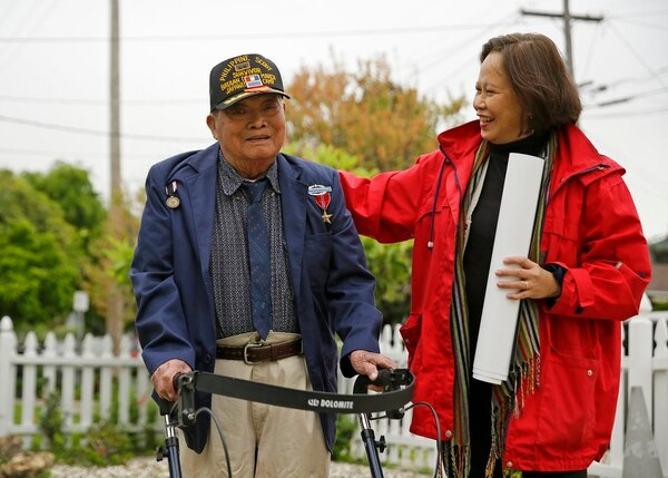 In this Thursday, April 6, 2017, file photo, Bataan Death March survivor Ramon Regalado walks with Cecilia Gaerlan outside his home in El Cerrito, Calif. Regalado died Dec. 16, 2017, said Gaerlan, executive director of the Bataan Legacy Historical Society. He was 100. (Eric Risberg/AP)