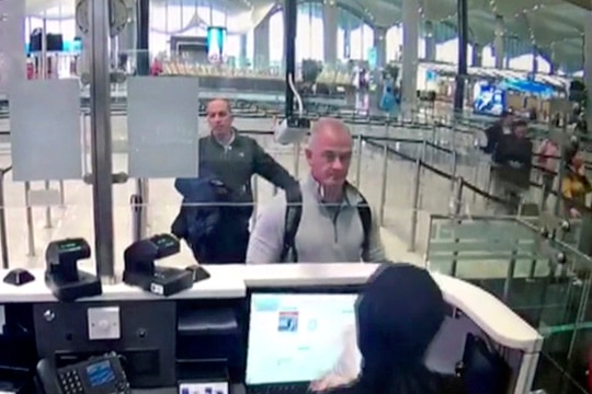 This Dec. 30, 2019, image from security camera video shows Michael L. Taylor, center, and George-Antoine Zayek at passport control at Istanbul Airport in Turkey. T(DHA via AP)