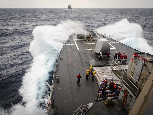 Sailors observe from the foc's'le as the guided-missile destroyer John S. McCain makes its approach towards the dry cargo and ammunition ship Alan Shepard prior to a replenishment-at-sea on Oct. 22 in the South China Sea. (MC2 Markus Castaneda/Navy)