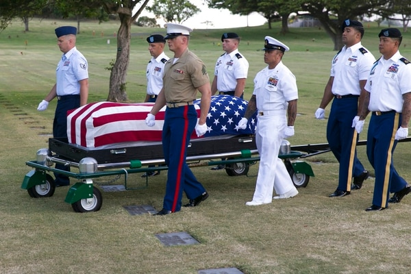 In this July 27, 2015, file photo, military pallbearers escort the exhumed remains of unidentified crew members of the USS Oklahoma killed in the 1941 bombing of Pearl Harbor that were disinterred from a gravesite at the National Memorial Cemetery of the Pacific in Honolulu. (Marco Garcia/AP)