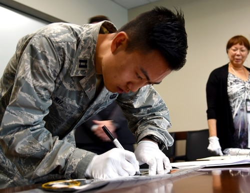 Air Force Capt. Patrick Wu signed the thermal space blanket that will protect parts of the AEHF-4 satellite when it launches. (Walter Talens/Air Force)