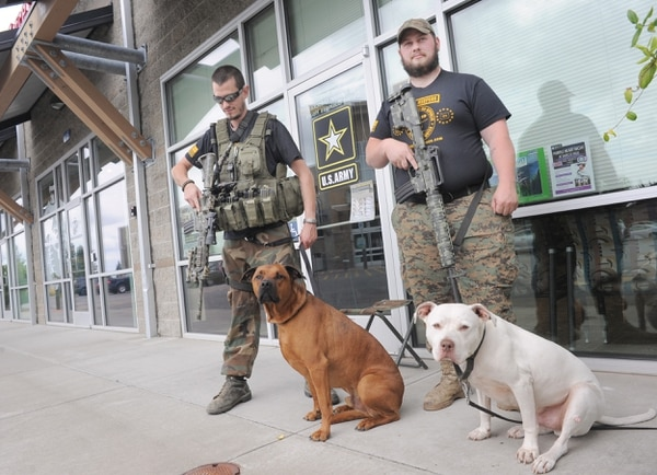 Oath Keepers Greg Schillen (left) and Adam Bulder stand guard Wednesday, July 22, 2015 in front of the military recruitment offices at the corner of Burlington Boulevard and Rio Vista Avenue in Burlington, Wash. with Schillen's two dogs Clyde (left) and Buddy. The two men wanted to stand in protection of the offices in light of the tragedy last week in Tennessee where five people were killed as a recruitment office was assaulted by a gunmen. Oath Keepers is a non-partisan association of current and formerly serving military, police, and first responders who pledge to fulfill the oath all military and police take to Òdefend the Constitution against all enemies, foreign and domesticÓ according to the group's web site. (Scott Terrell / Skagit Valley Herald via AP)