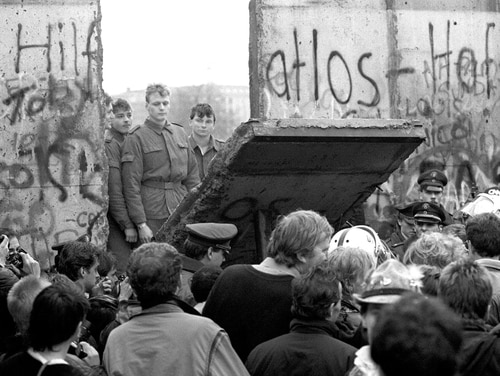 BERLIN, GERMANY: (FILES) West Berliners crowd in front of the Berlin Wall early 11 November 1989 as they watch East German border guards demolishing a section of the wall in order to open a new crossing point between East and West Berlin, near the Potsdamer Square. The day before, Gunter Schabowski, the East Berlin Communist party boss, declared that starting from midnight, East Germans would be free to leave the country, without permission, at any point along the border, including the crossing-points through the Wall in Berlin. Germany will celebrate 09 November 2004 the 15th anniversary of the wall's fall. AFP PHOTO FILES/GERARD MALIE (Photo credit should read GERARD MALIE/AFP/Getty Images)