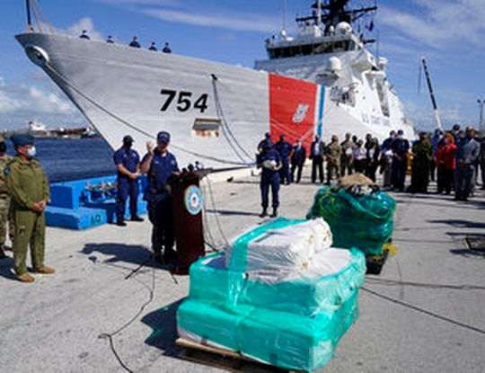 Vice Adm. Steven Poulin, at podium, Atlantic Area Commander, U.S. Coast Guard, speaks during a news conference in front of the Coast Guard Cutter James and pallets of cocaine, Thursday, Aug. 5, 2021, at Port Everglades in Fort Lauderdale, Fla. (AP Photo/Wilfredo Lee)