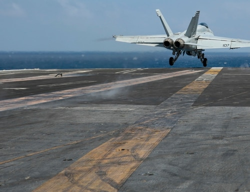 An F/A-18E Super Hornet from the Pukin' Dogs of Strike Fighter Squadron 143 launches from the flight deck of the aircraft carrier Abraham Lincoln on Christmas Eve in the South China Sea. (Mass Communication Specialist 3rd Class Michael Singley/Navy)