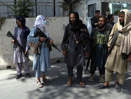 Taliban fighters stand guard at the main gate leading to the Afghan presidential palace in Kabul, Afghanistan, on Aug. 16, 2021. (Rahmat Gul/AP)