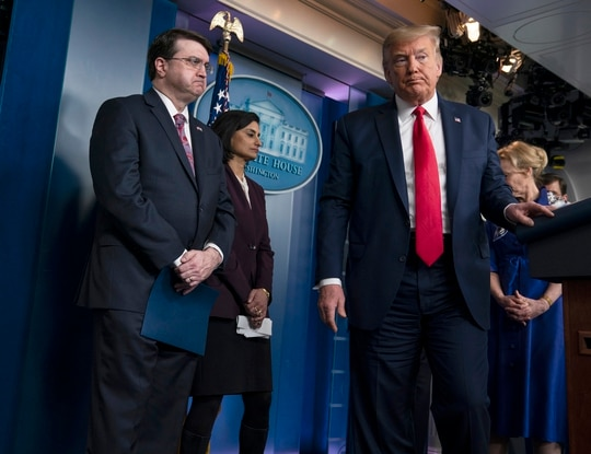 President Donald Trump departs after a press briefing with the coronavirus task force at the White House on March 18, 2020, as Veterans Affairs Secretary Robert Wilkie (left) looks on. (Evan Vucci/AP)