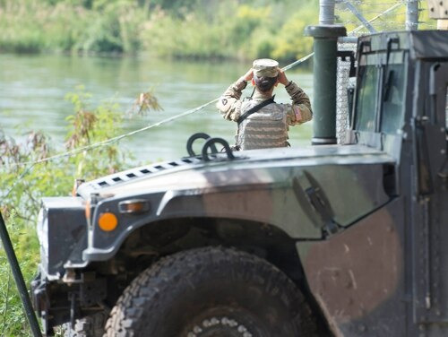 A soldier from the Texas National Guard scans the shores of the Rio Grande River in Starr County, Texas, April 10, 2018, as part of the federal call-up to the Texas-Mexico border. Soldiers called to duty at the border support federal partners and primarily serve in observe. (Sgt. Mark Otte/National Guard)