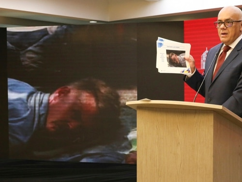 In this photo released by the Venezuelan officials, Communications Minister Jorge Rodriguez shows a photograph of a man he identifies as former U.S. special forces soldier Luke Denman and taken in Venezuela during his arrest, in Caracas, Venezuela, Tuesday, May 5, 2020. (Venezuelan Communications Ministry press office via AP)