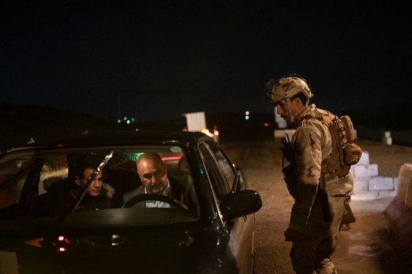 In this April 2, 2019, photo, an Iraqi army 20th division soldier asks for documents at a checkpoint near Badoush, Iraq. (Felipe Dana/AP)
