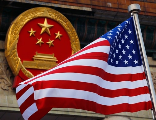 An American flag is flown next to the Chinese national emblem. (Andy Wong/AP)