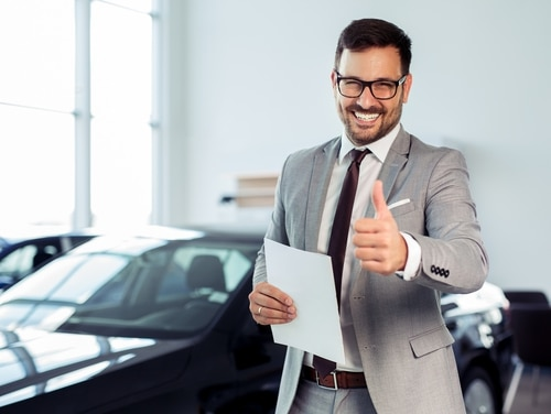 'Congrats on your new busted car and thanks for letting me ruin your life,' an enthused auto salesman near a military base says. (Getty Images)