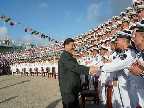 Chinese President Xi Jinping, center, meets with representatives of the aircraft carrier unit and the manufacturer at a naval port in Sanya, south China's Hainan Province, on Tuesday. (Li Gang/Xinhua News Agency via AP)