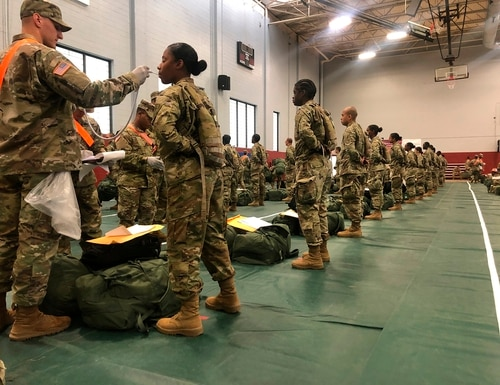 Recent Army basic combat training graduates have their temperatures taken as they arrive at Fort Lee, Va., on March 31, 2020, after being transported using sterilized buses from Fort Jackson, S.C. (U.S. Army via AP)