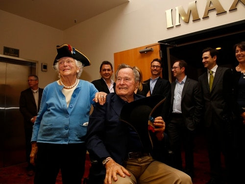 Former President George H.W. Bush, center, and former first lady Barbara Bush, left, show off the tri-corner hats that they received as a gift from the cast of AMC's new series TURN during a private screening on March, 29, 2014, in Houston, Texas. (Aaron M. Sprecher/AP)