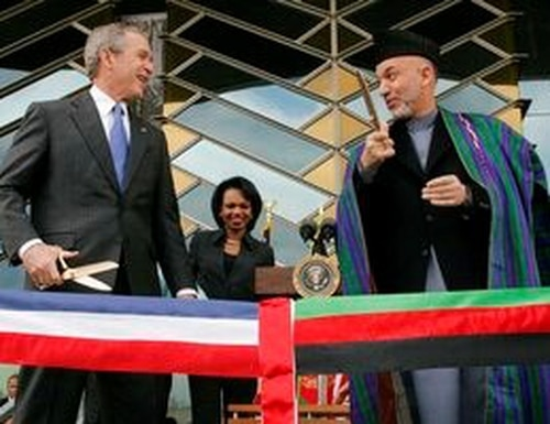 FILE - In this March 1, 2006 file photo, U.S. President George W. Bush, left and Afghan President Hamid Karzai get ready to cut a ribbon to officially open the U.S. Embassy in Kabul, Afghanistan. (AP Photo/Charles Dharapak, File)