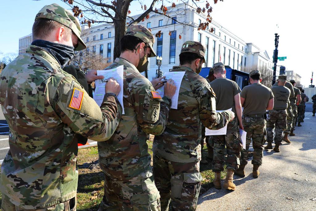Soldiers in the Maryland Army National Guard use the back of the soldiers in front of them to fill out their medical paperwork to receive the COVID-19 vaccine at the U.S. Capitol Complex in Washington on Jan. 14, 2021.