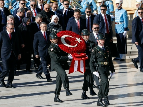 Turkey's President Recep Tayyip Erdogan, second left, follows a military honor guard walking toward the mausoleum of Turkey's founder Mustafa Kemal Ataturk on Republic Day in Ankara, Turkey, Monday, Oct. 29, 2018. Kurdish fighters in Syria said Wednesday, Oct. 31, that Turkey's military attacks in Syria are getting in the way of their fight against ISIS. (AP Photo/Burhan Ozbilici)