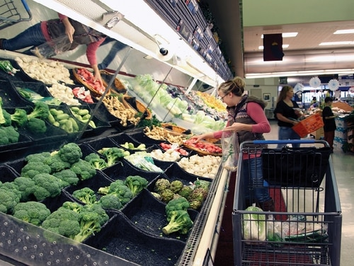 A military family member selects vegetables from the produce section in the Camp Foster commissary in 2013, before a new purchasing process for produce took effect that affected price and quality. (Photo by Lance Cpl. Elizabeth Casez/Marine Corps)