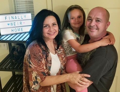 The Weir family, Vennita, left, Athena, center, and Bill take a photograph, at their home on Wednesday, September 27, 2018, in Albuquerque, N.M. Military families are complaining that this year's base transfers are the worst in memory as movers are destroying, damaging, losing and stealing their household goods. (Vennita Weir via AP)