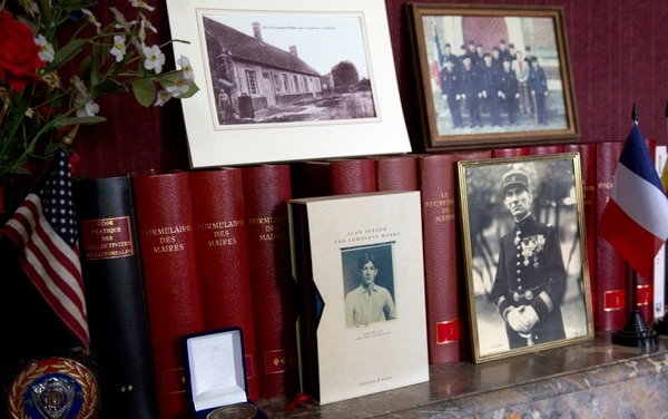 In this photo taken on Wednesday, June 8, 2016, a photograph of American poet Alan Seeger and other mementos line a mantle piece in the Mayors office of Belloy-en-Santerre, France. American poet Alan Seeger died a century ago on July 4th during the 1916 Battle of the Somme in northern France, already fighting for a global, common cause that bound dozens of countries together at a time when the United States was still a bystander, reluctant to get involved in a faraway war. (AP Photo/Virginia Mayo)