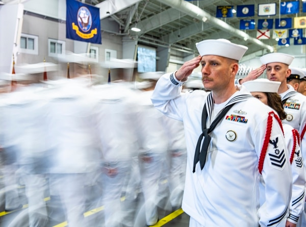 Recruit division commanders salute graduating divisions as they enter Midway Ceremonial Drill Hall during a pass-in-review graduation ceremony on June 14 at Recruit Training Command. (Mass Communication Specialist 1st Class Spencer Fling/Navy)