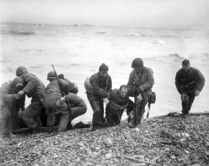 members of an American landing unit help their comrades ashore during the Normandy invasion