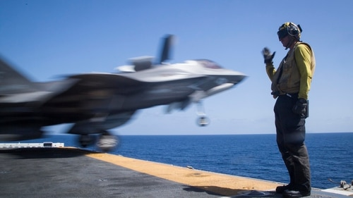 GULF OF ADEN - U.S. Navy Petty Officer 3rd Class Alex Rock, an aviation boatswain mate handler with the Essex Amphibious Ready Group (ARG), salutes an F-35B Lightning II during takeoff from the Wasp-class amphibious assault ship USS Essex (LHD 2), Sept. 22, 2018. The Essex is the flagship for the Essex Amphibious Ready Group and, with the embarked 13th MEU, is deployed to the U.S. 5th Fleet area of operations in support of naval operations to ensure maritime stability and security in the Central Region, connecting the Mediterranean and the Pacific through the western Indian Ocean and three strategic choke points. (U.S. Marine Corps photo by Cpl. Francisco J. Diaz Jr./Released)
