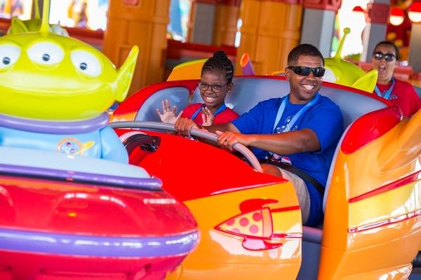 Marine GySgt Harry Johnson and his daughter ride Alien Swirling Saucers as part of a special advance preview of Toy Story Land at Disney's Hollywood Studios. On Alien Swirling Saucers, guests climb aboard their rocket ships and swirl about trying to get caught by the ominous Claw from the Toy Story movies. The ride features multi-colored lighting, music and sound effects. (Disney)