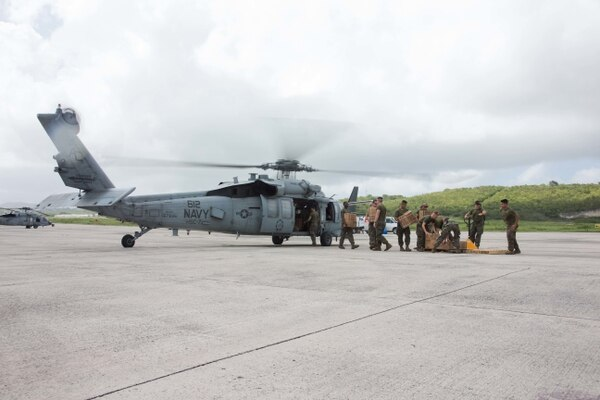Marines with Battalion Landing Team 2nd Battalion, 6th Marine Regiment, 26th Marine Expeditionary Unit, unload emergency provisions from a Navy MH-60S Seahawk helicopter with Helicopter Sea Combat Squadron 7, at the Henry E. Rohlsen Airport in St. Croix, U.S. Virgin Islands, Sept. 11. (Lance Cpl. Alexis C. Schneider/Marine Corps)