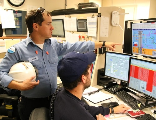 BSEE Inspector Sammy Viola points at a computer monitor where a Murphy Oil representative oversees subsea infrastructure from the Front Runner control room. (Bureau of Safety and Environmental Enforcement)
