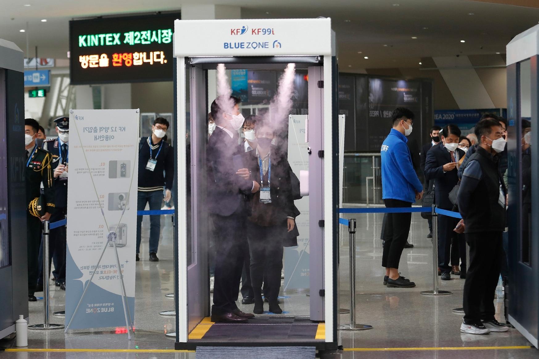 An attendee of DX Korea 2020 stands in a sterilizer as a precaution against the novel coronavirus on Nov. 18, 2020. (Ahn Young-joon/AP)