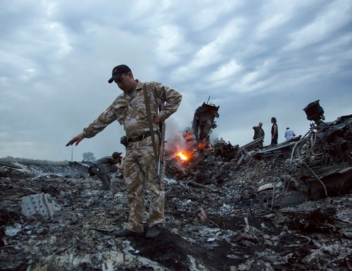 People walk among the debris at the crash site of Malaysia Airlines Flight 17 near the village of Grabovo, Ukraine, on July 17, 2014. (Dmitry Lovetsky/AP)