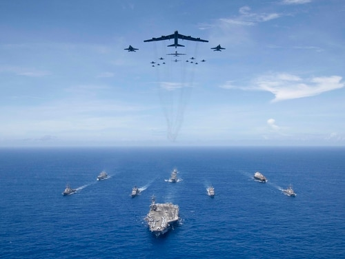 The aircraft carrier Ronald Reagan, foreground, leads a formation of Carrier Strike Group Five ships as Air Force B-52 Stratofortress aircraft and Navy F/A-18 Hornet aircraft pass overhead during Valiant Shield 2018 in the Philippine Sea on Sept. 17, 2018. (MC3 Erwin Miciano/U.S. Navy)