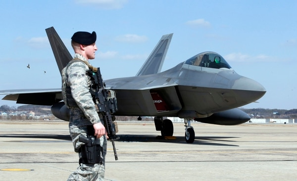 U.S. Air Force military police stand guard near a U.S. F-22 stealth fighter after landing at Osan Air Base in Pyeongtaek, South Korea, in 2016. The presence of the F-22s at the Max Thunder 2018 training exercise has allegedly contributed to North Korea threatening to withdraw from a historic summit with the Trump administration next month. (Lee Jin-man/Associated Press)