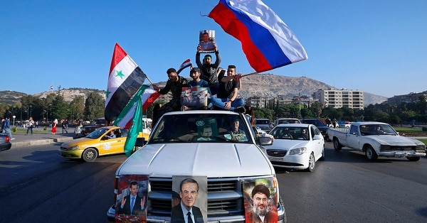 Syrian government supporters wave Syrian, Iranian and Russian flags as they chant slogans against U.S. President Trump during demonstrations following a wave of U.S., British and French military strikes to punish President Bashar Assad for suspected chemical attack against civilians, in Damascus, Syria, Saturday, April 14, 2018. (Hassan Ammar/AP)