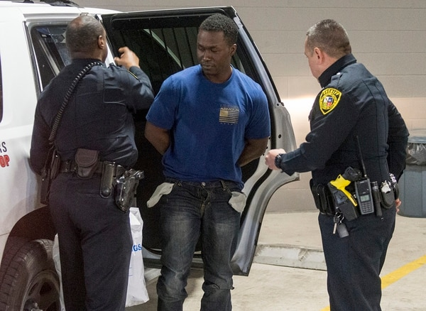 Air Force Major Andre McDonald, center, is escorted Sunday, March 3, 2019, to the Bexar County Magistrate center where where Sheriff Javier Salazar says he will be charged with tampering with evidence in the disappearance of his 29-year-old wife, Andreen McDonald. (William Luther/The San Antonio Express-News via AP)