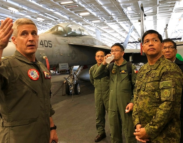 Rear Adm. Steve Koehler, left, commander CSG-9 of the U.S. aircraft carrier Theodore Roosevelt, briefs top Philippine generals led by Lt. Gen. Rolando Joselito Bautista, foreground right, Tuesday, April 10,2018, in international waters off South China Sea. The aircraft carrier CVN-71 is sailing through the disputed South China Sea in the latest display of America's military might after China built a string of islands with military facilities in the strategic sea it claims almost in its entirety. (Jim Gomez/AP)