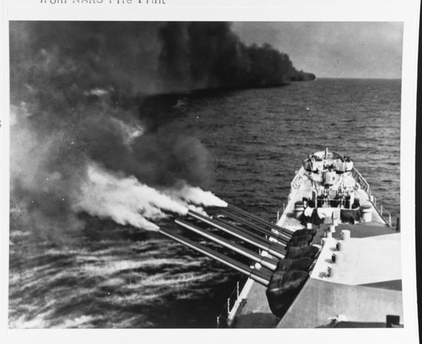 The heavy cruiser Quincy fires its forward 8/55 guns off Toulon, France, while supporting the invasion, 16 August 1944. Note smoke screen laid by the ship next ahead to prevent accurate counter-fire by German coastal artillery. (National Archives)