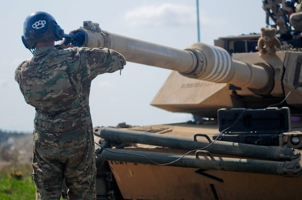 A tank crew member bore sights the barrel of his M1A2 Abrams tank before a live-fire training exercise in Poland. (Sgt. Lisa Vines/Army)