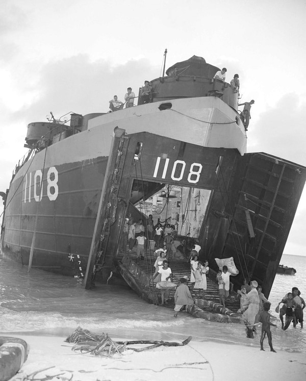 In this March 14, 1946 file photo, natives of Bikini Atoll, scene of upcoming atomic tests, go ashore on the beach at Rongerik Atoll, their new home, after being moved in a Navy LST. (Clarence Hamm/AP)