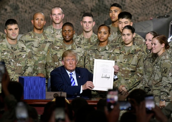 President Donald Trump signs the John McCain National Defense Authorization Act for the Fiscal Year 2019, during a signing ceremony Monday, Aug. 13, 2018, at Fort Drum, N.Y. (AP Photo/Hans Pennink)