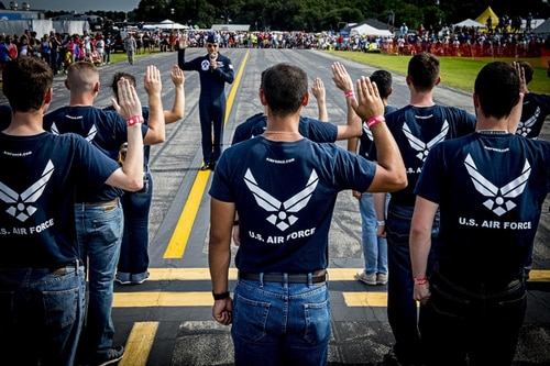 Maj. Tyler Ellison, an Air Force Thunderbirds pilot, administers the Oath of Enlistment to a group of new airmen during an air show in Florida. (Tech. Sgt. Manuel J. Martinez/Air Force)