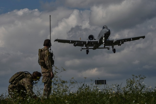 Two U.S. Air Force combat controllers with the 321st Special Tactics Squadron observe an A-10 Thunderbolt II landing on Jägala-Käravete Highway, Aug. 10, 2017, in Jägala, Estonia. (Senior Airman Ryan Conroy/Air Force)