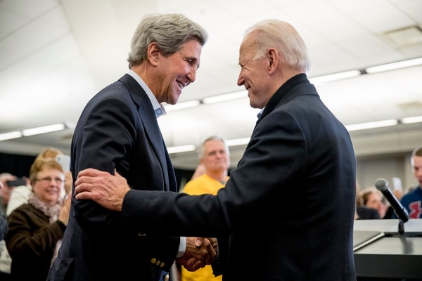 In this Feb. 1, 2020, file photo Democratic presidential candidate former Vice President Joe Biden smiles as former Secretary of State John Kerry, left, takes the podium to speak at a campaign stop at the South Slope Community Center in North Liberty, Iowa. (Andrew Harnik/AP)