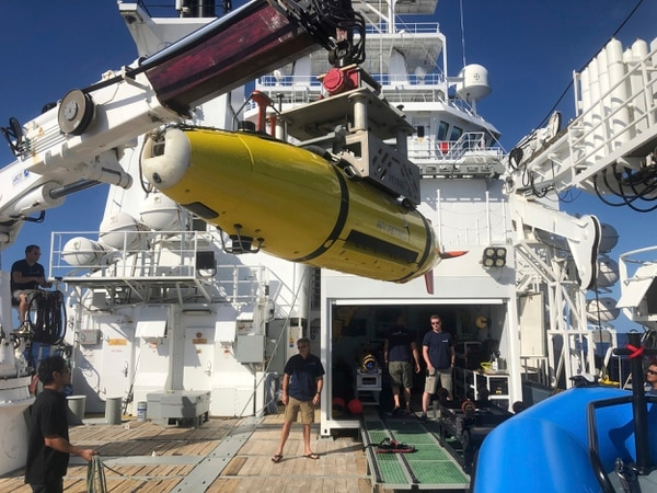 An autonomous underwater vehicle carrying high frequency sonar images of the Japanese aircraft carrier Akagi is loaded onto the research vessel Petrel on Sunday off Midway Atoll in the Northwestern Hawaiian Islands. (Caleb Jones/AP)