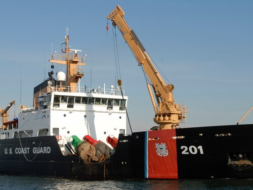 The deck crew of the Coast Guard Cutter Juniper maintaining a buoy in the Sandy Hook Channel in 2006. (U.S. Coast Guard)